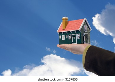 Miniature house in woman hand held against blue skies - real estate concept