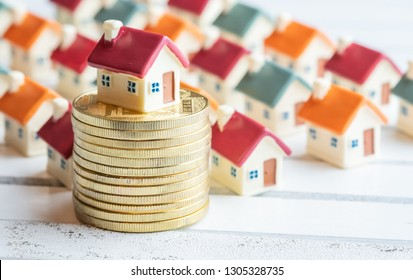 Miniature houses with coins on wooden board. Property investment conceptual image.