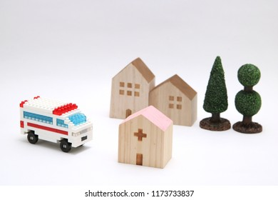 Miniature houses, hospital and ambulance on wood. Emergency transport concept.
