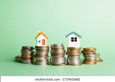 Miniature houses on coins, mortgage concept.