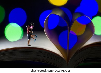 Miniature hugging couple on a book, book lover with bokeh background