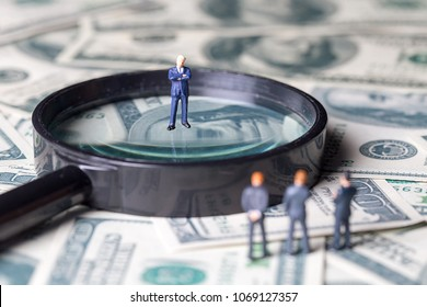 Miniature of investor man stand on money and magnifying glass in back. Business and Investment concept.