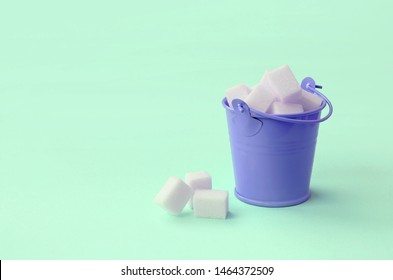 A miniature lilac bucket filled with cubes of sugar lies on a turquoise pastel background