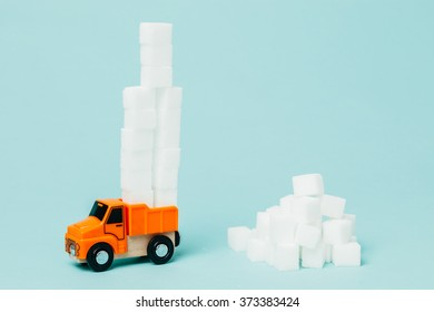 Miniature lorry picking huge sugar amount. Conceptual image about food industry and sugar.
