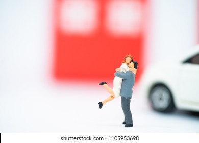 Miniature lover couple,couple hugging front of new house and new car.Valentine's day concept.