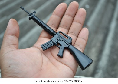 Miniature M16 toy gun model placed in the palm of the hand