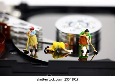 Miniature maids or cleaning women on an open computer hard drive. They are cleaning viruses, spyware and trojans. Computer anti-virus and security concept.