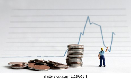 A miniature man and coins with a linear graph.