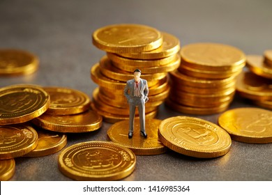 Miniature man with gold coins