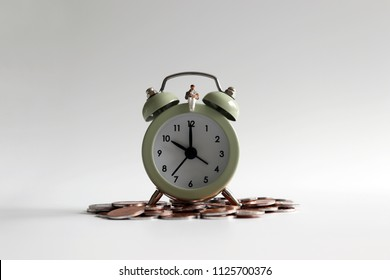 A miniature man holding a baby sitting on an alarm clock with coins.