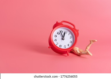 A miniature man lies behind a red alarm clock on a pink background. Abstract concept of waking up in the morning. Deadline. Procrastination.