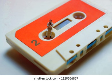 Miniature man on a retro, vintage, 1980's audio cassette. Man is listening or recording music or conversation. Old, obsolete, analogue technology.