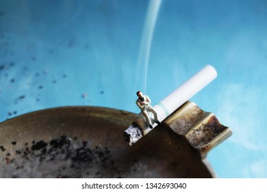 Miniature man on a smoking cigarette.Man takes a little smoke break.The struggle to quit can be a huge challenge and overwhelming, Macro image showing a bad habit. Small amounts of tobacco are harmful