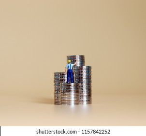 Miniature man with piles of coins.