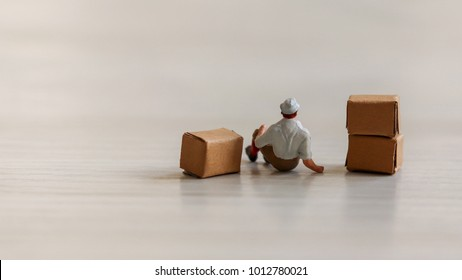 A miniature man relaxing next to a stacked box.