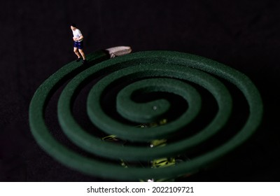 Miniature man running on mosquito coil
