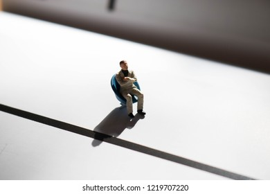 Miniature man seated on isolated white background. Shadowy or shady person. Person with dramatic, moody shadows that conveys a sad or lonely feeling. Worker or businessman in the spotlight.