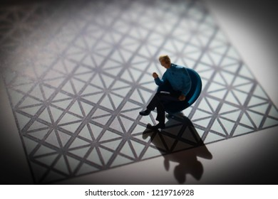 Miniature man sitting with grid or web background. Businessman concealed in heavy, mysterious, shadows. Person with no identity.