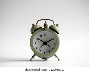 A miniature man sitting on the alarm clock.