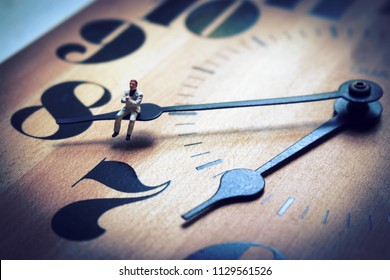 Miniature man sitting on the hands of a clock. Concept of waiting or running out of time. Work or business deadline is ticking away. Employee or boss struggles with time management.