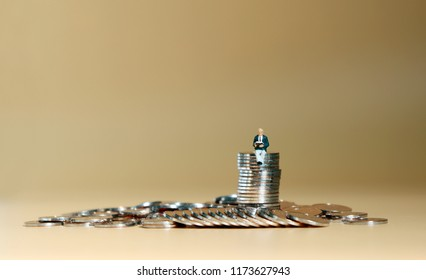 Miniature man sitting on a pile of coins reading a book.