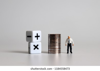 Miniature man standing with a cube with a mathematical symbol and a pile of coins.