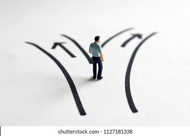 A miniature man standing in front of two roads.