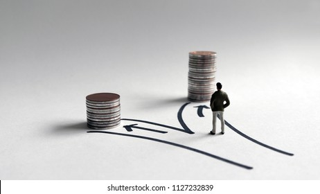 A miniature man standing in front of two paths with a stack of coins of different heights.