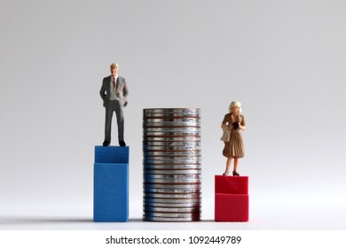 A miniature man standing on the high blue stairs on either side of a pile of coins and a miniature woman standing on the low red stairs.