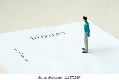 miniature man standing on a paper sheet with to do list. planning. buiseness