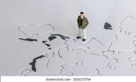 A miniature man standing on a world map.
