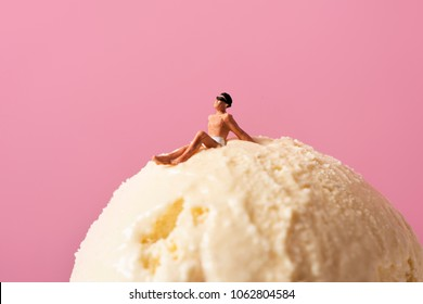 a miniature man wearing swimsuit relaxing on an ice cream ball, against a pink background with some blank space on top