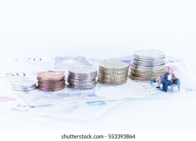 Miniature man and woman sitting on a bench besides the coins close up