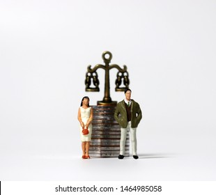 A miniature man and a miniature woman standing in front of a pile of coins with a miniature scale.