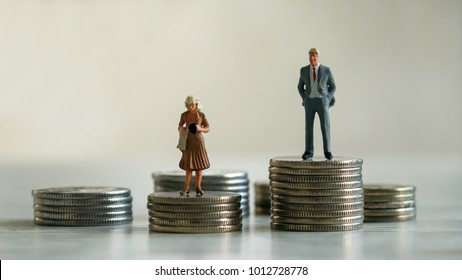 Concept of gender discrimination in pay. A miniature man and miniature woman standing on top of a pile of coins.