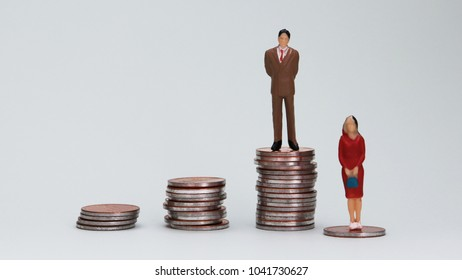 Genderwagedifferenceconcept. A miniature man and a woman standing on top of a pile of coins.