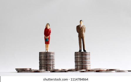 A miniature man and a miniature woman standing on a stack of coins of the same height.