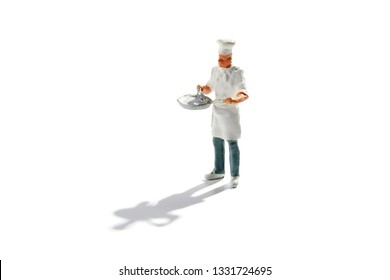 Miniature master chef in toque and apron with a pan in his hands isolated on white with copy space and shadow