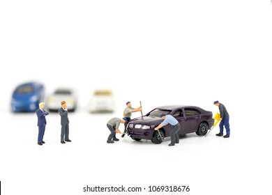 Miniature mechanics repairing toy car,concept of the workshop