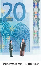 Miniature men chatting with the Euro banknote at the background