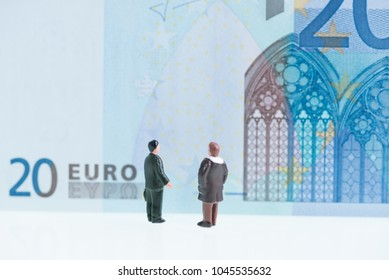 Miniature men looking at the Euro banknote