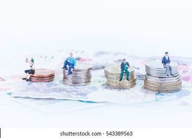 Miniature men sitting on stacked of coins and banknotes