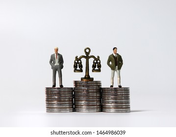 Miniature men standing on a pile of coins of the same height. Pile of coins and a miniature scale.