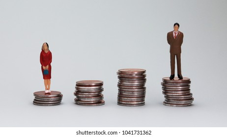 Genderwagedifferenceconcept. The miniature men and women are standing on the coin tower.