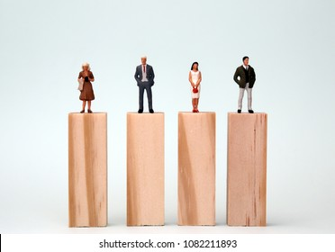 Miniature men and women standing on the same height block. The concept of equal opportunities for gender.