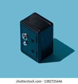 Miniature metallic locked black safe: bank deposit and security concept