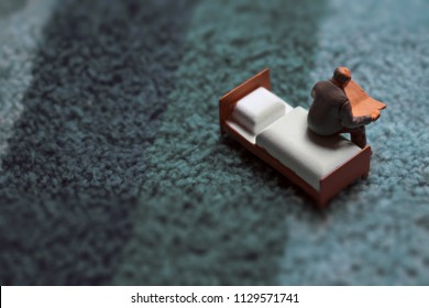 Miniature middle aged or elderly man reads on a tiny bed.  Man in his home with vintage shag rug texture. Sitting down with a good novel, newspaper, or magazine.