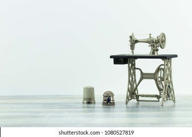 Miniature model of beautiful vintage sewing machine and two old thimbles will be presented on rustic bright table. Isolated. Advertisment for tailor business. Space for text and montage. Card.