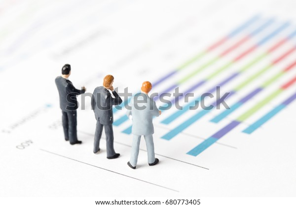 Miniature model of businessman thinking with project for presenting investment concept on graph.