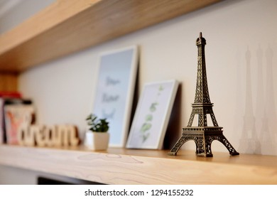 miniature model of a golden Eiffel tower on a shelf .